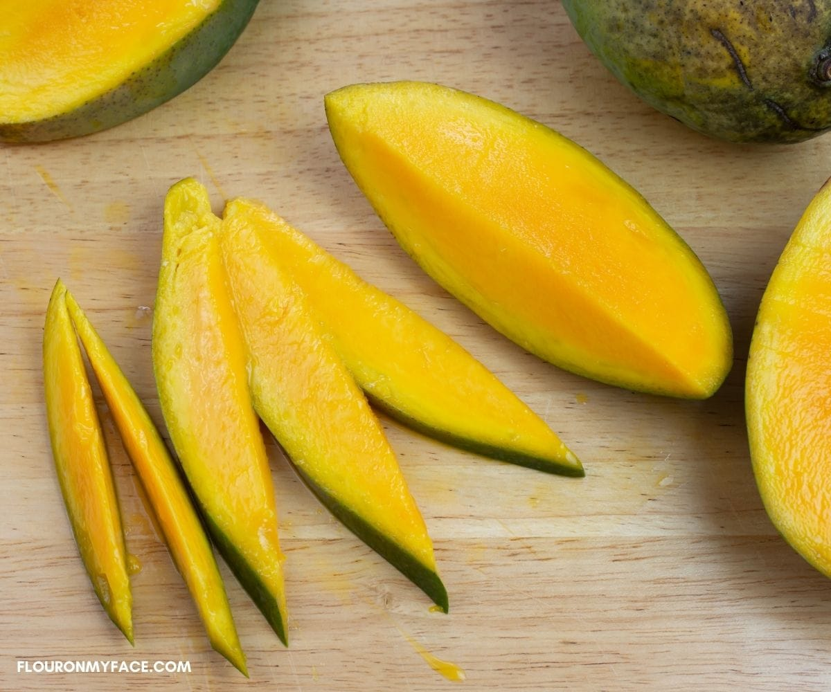 Cutting fresh mango into thin slices before drying.