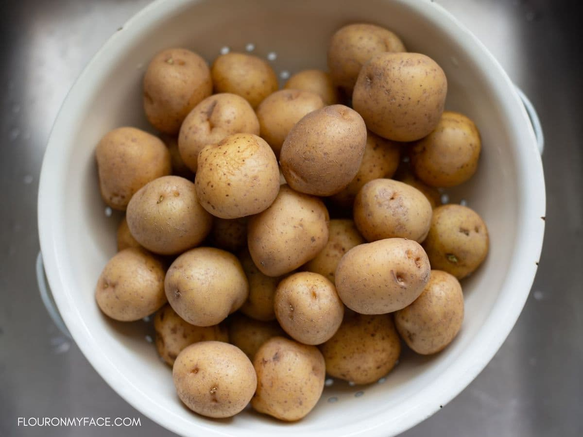 A colander filled with new baby potatoes in the sink.