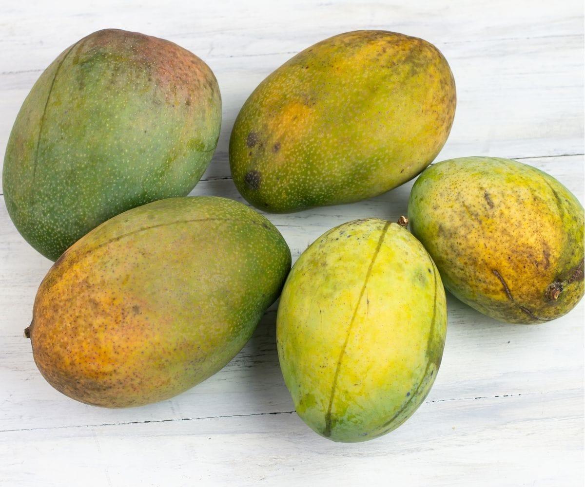 5 Fresh mangos on a table top.