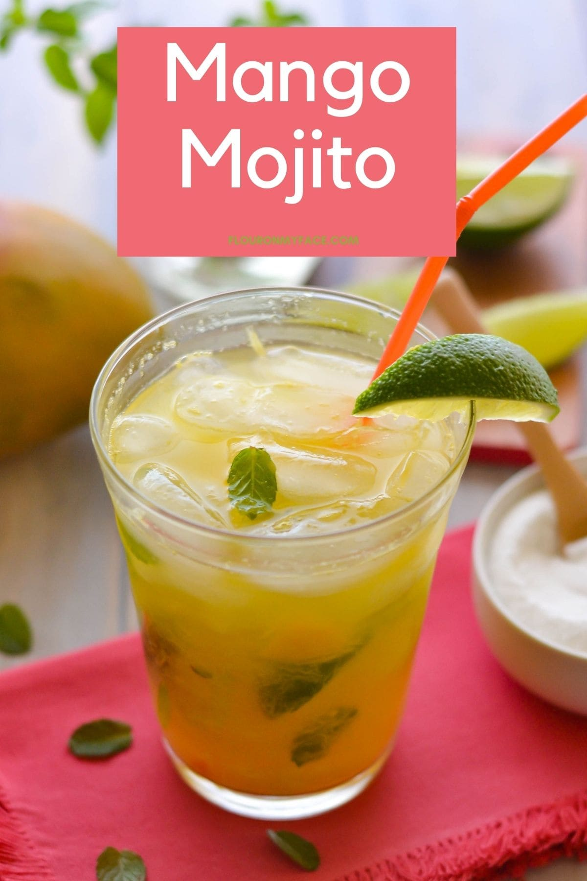 A tall glass filled with Mango Mojito garnished with lime on a cloth napkin.