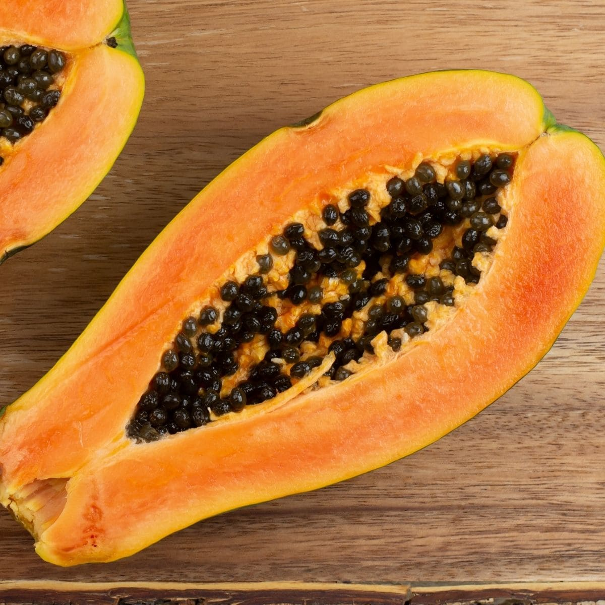 A large fresh papaya cut in half on a wooden cutting board.