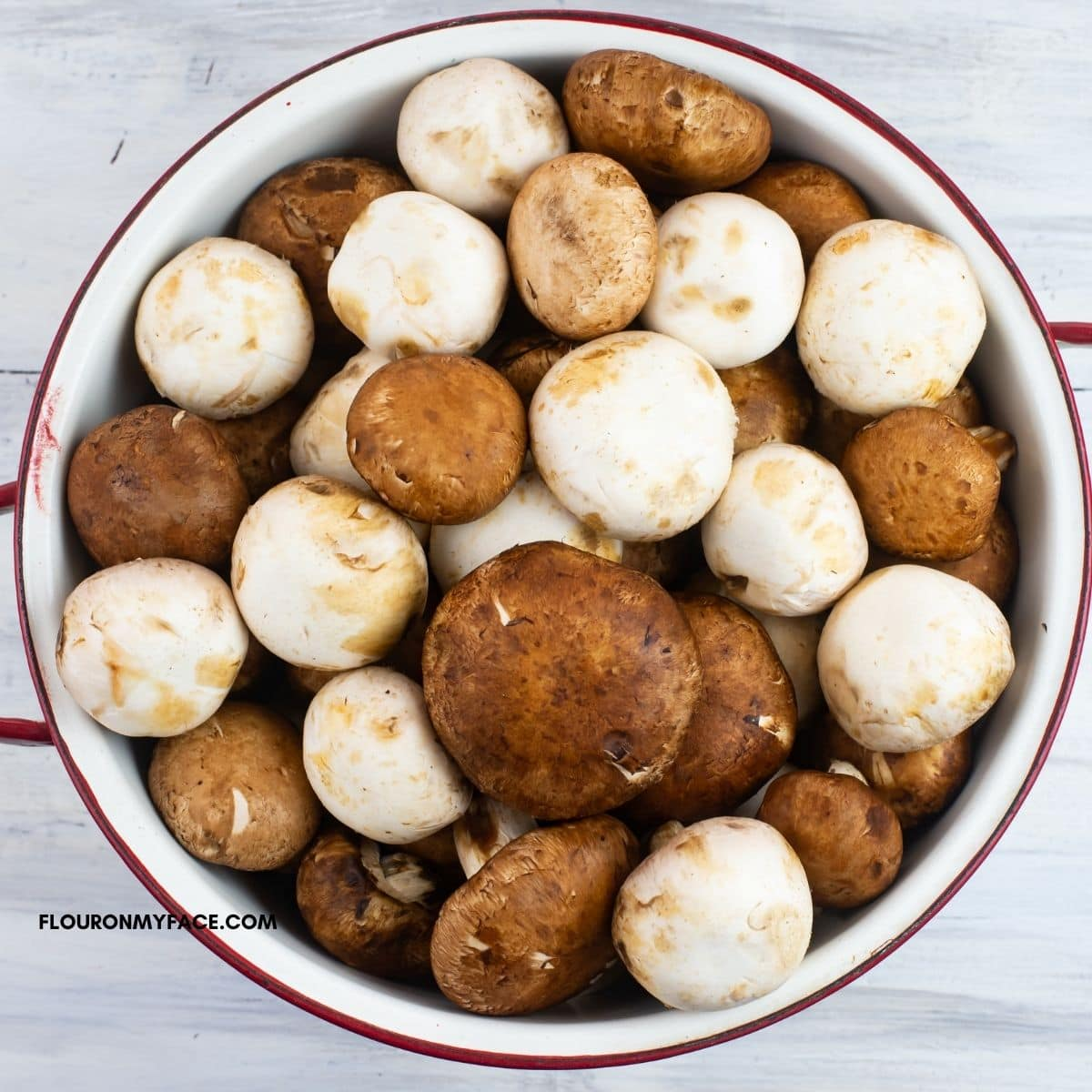 A white metal colander filled with white and baby portabella mushrooms.