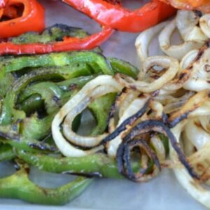 Grilled bell peppers and onions on a cookie sheet for grilled pizza toppings.