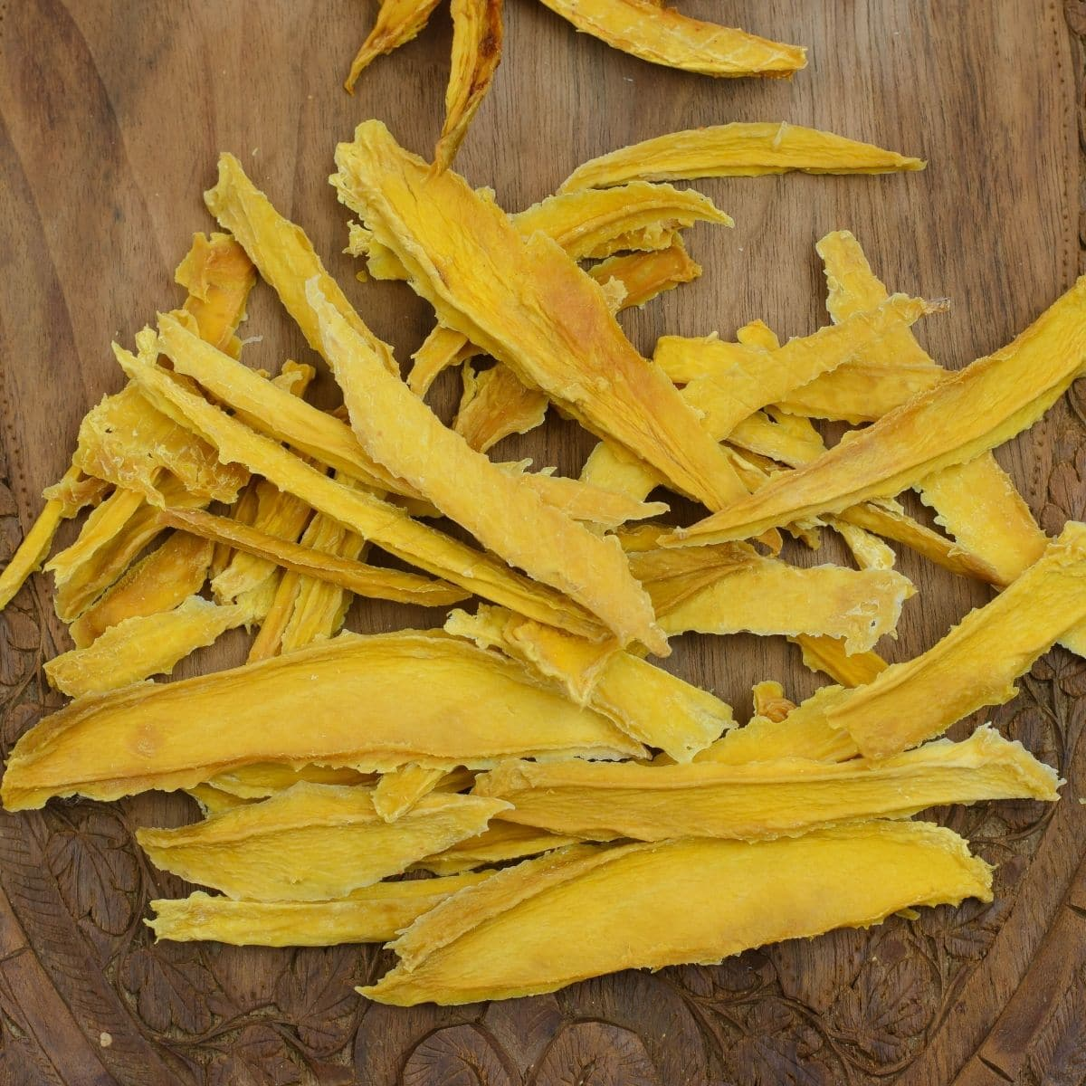 Dried sliced mango pieces on a wooden cutting board.