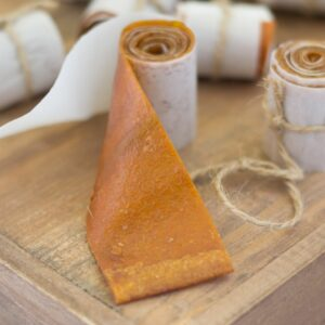 Homemade peach fruit leather roll ups on a wooden cutting board.
