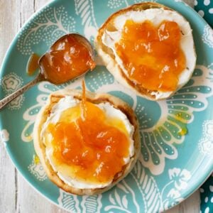 Toasted English Muffins with cream cheese and peach orange marmalade spread over the top on a teal glass plate.