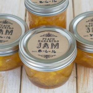 Canning jars filled with peach habanero jam on a table.