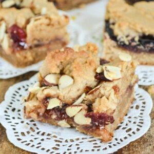 Peanut butter and jelly filled dessert bars on a wooden cutting board.