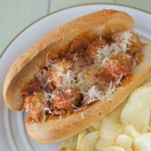 A Pepperoni Pizza Meatball Sub served with chips on a plate.