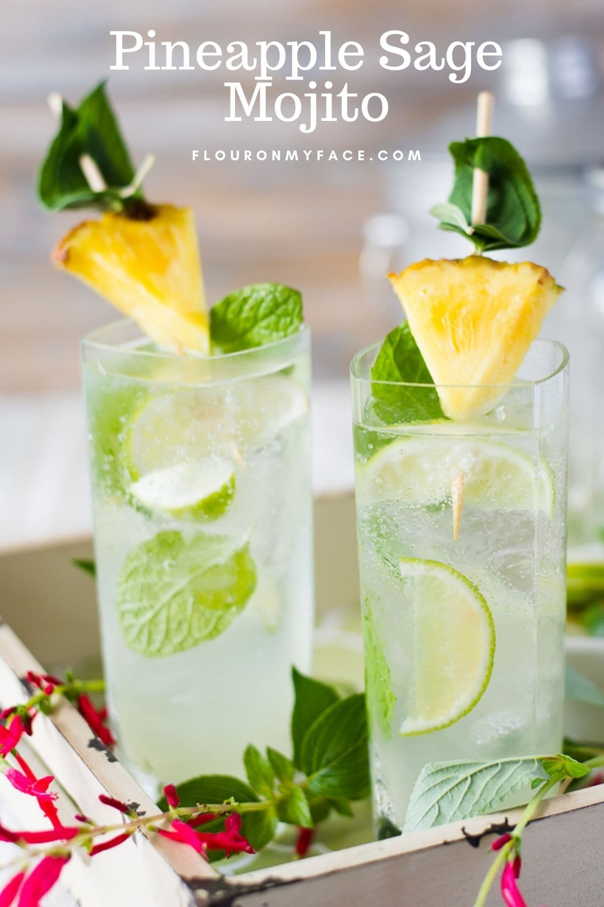 Two tall glasses on a serving tray filled with Pineapple Sage Mojito, garnished with pineapple wedges and mint leaves.
