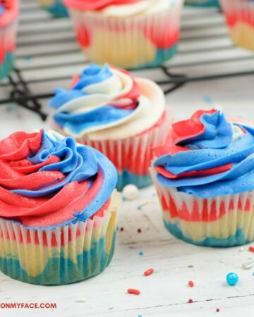 3 cupcakes decorated with red white and blue buttercream frosting.