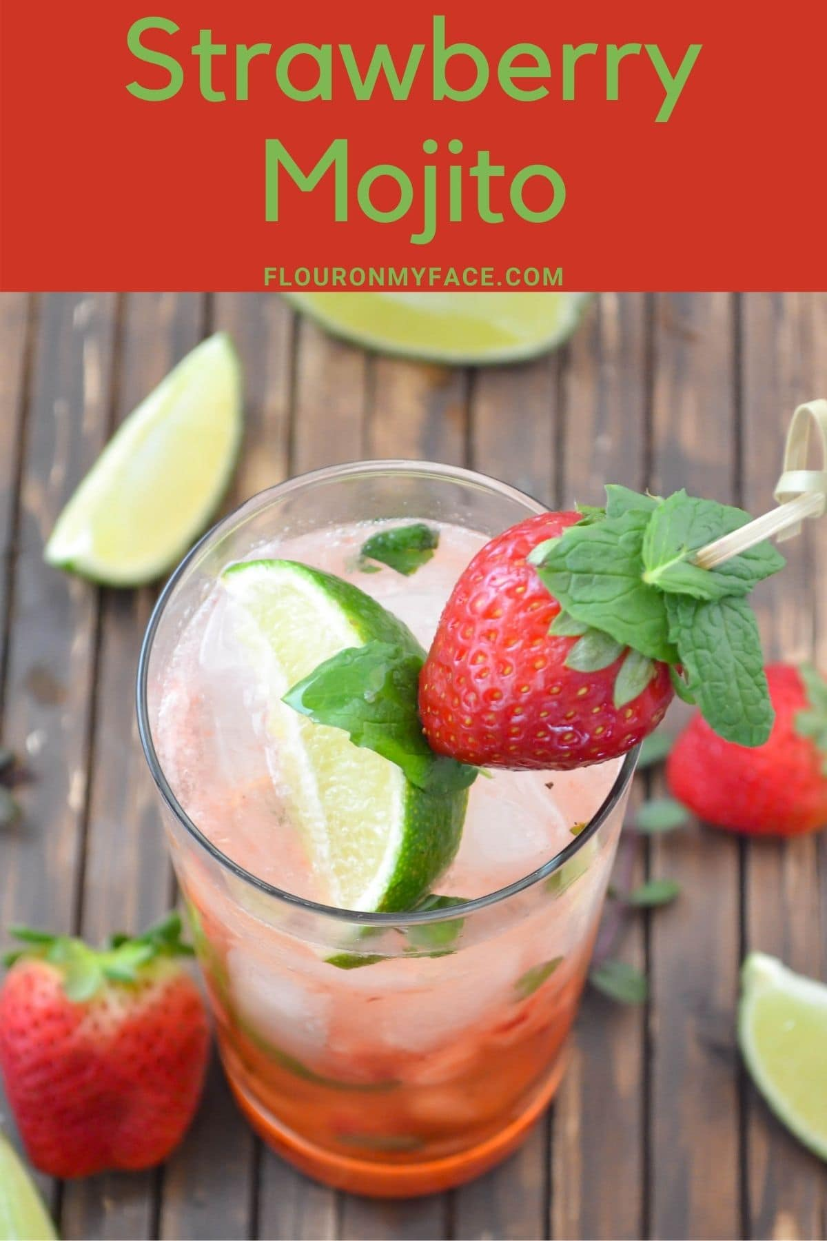 Tall glass filled with Strawberry Mojito garnished with a strawberry, lime wedge and mint.