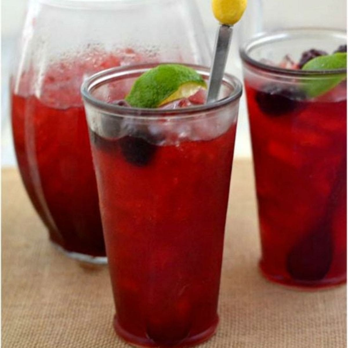 Two glasses and a pitcher filled with blackberry limeade.