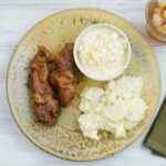 Country style pork ribs on a brown dinner plate with potato salad and coleslaw.