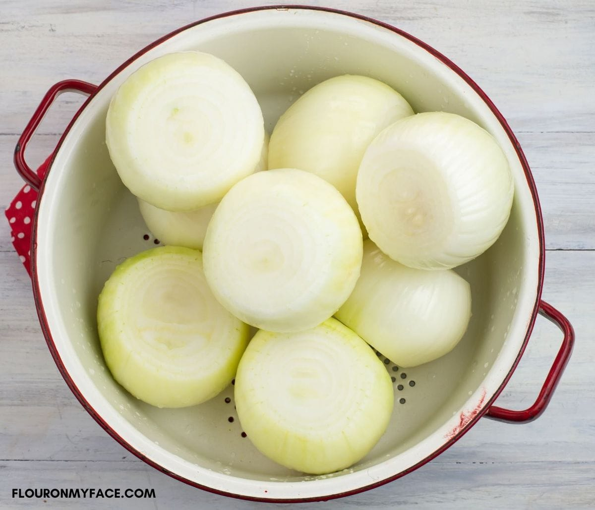 Large peeled white onions in a white enamel colander.