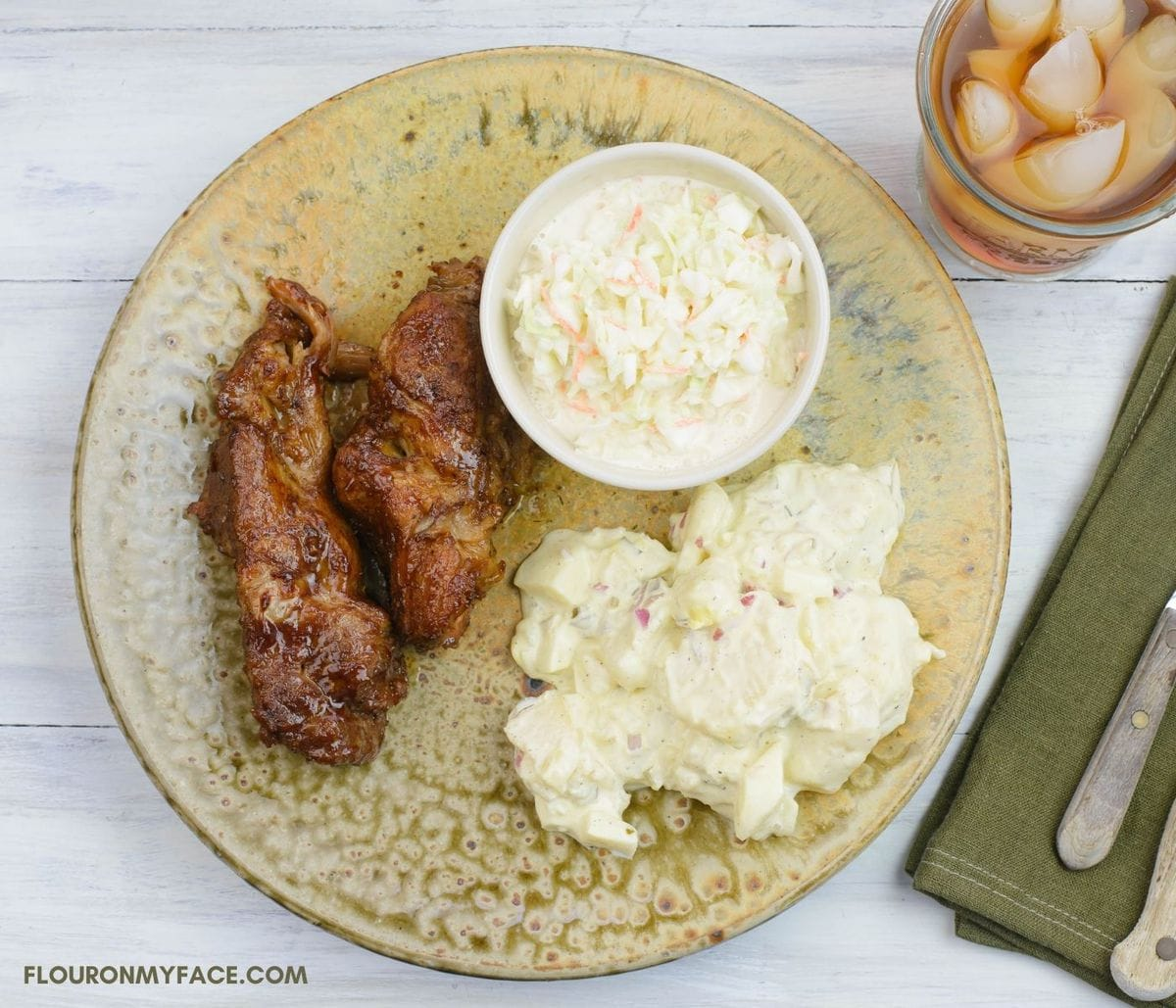 A dinner plate with a serving of Country style boneless pork ribs with two side dishes.