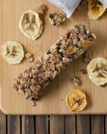 Banana Choclate Chip Granola bars on a wooden cutting board surrounded with dried banana chips.