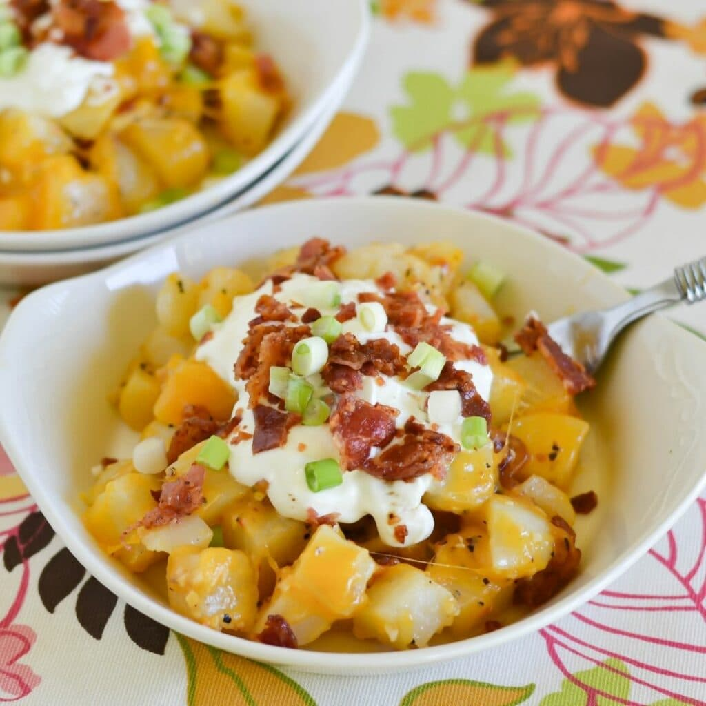 Small serving bowl filled with a Cheese Bacon Garlic Potato Side dish.