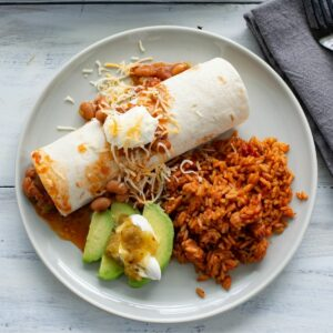 A dinner plate with crock pot chicken and bean burritos, sliced avocado and Spanish rice.