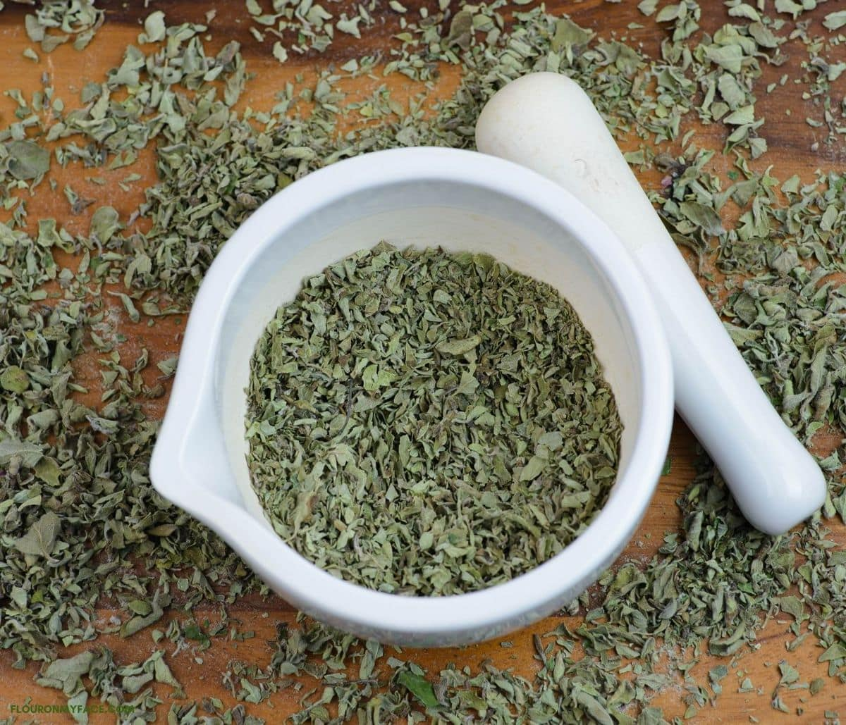 A tray with crushed dried oregano in a white mortar with a pestle.