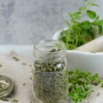 A spice jar filled with dried oregano.