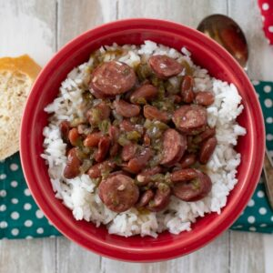 Serving red beans and rice in a red bowl on a teal napkin.