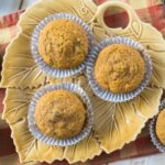 Three pumpkin cranberry muffins served on a leaf shaped plate.