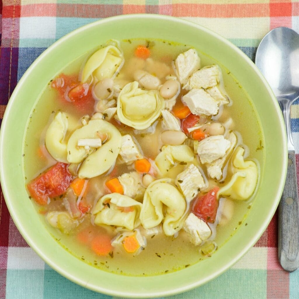 A green bowl filled with chicken tortellini white bean soup.