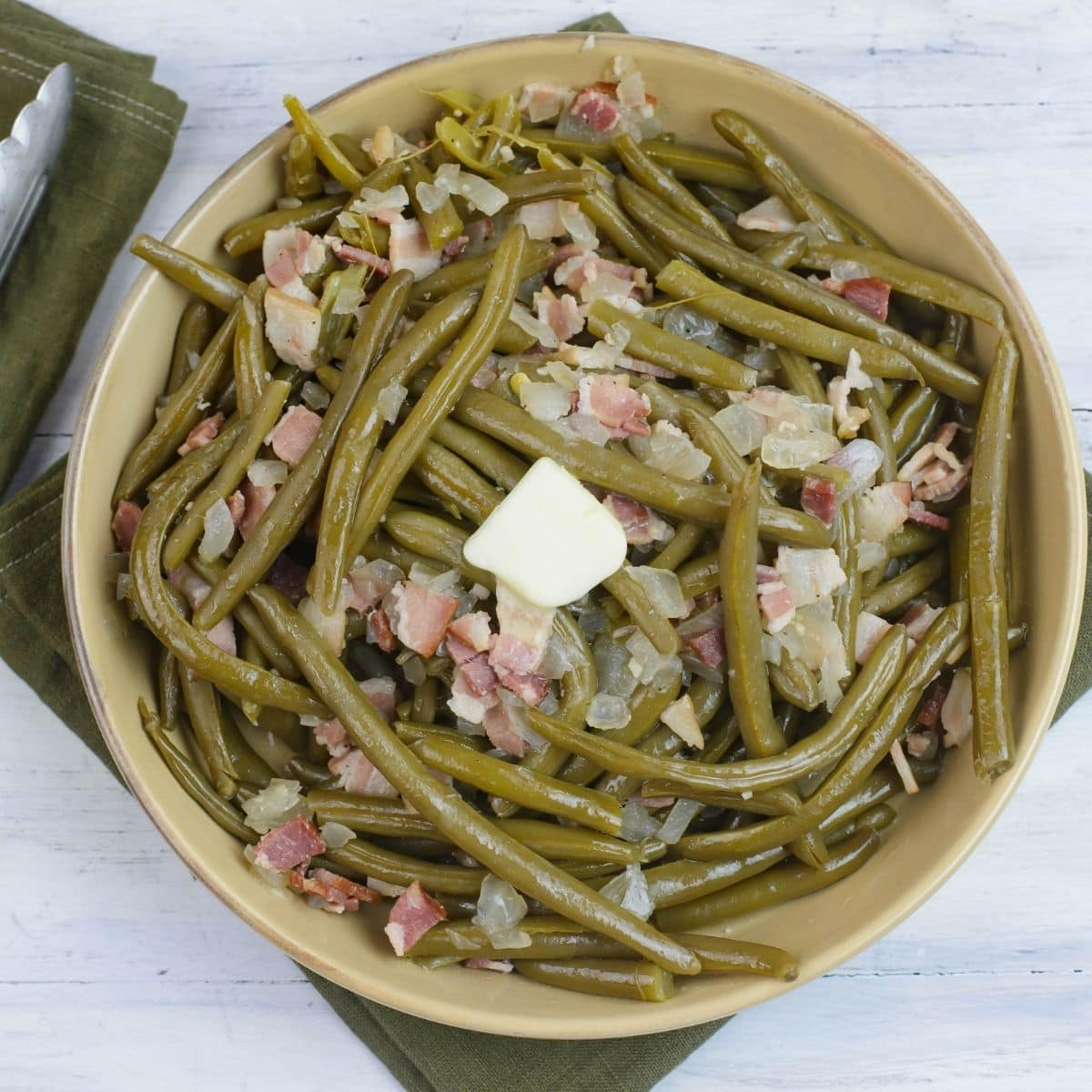 A large serving bowl filled with crock pot green beans with bacon.