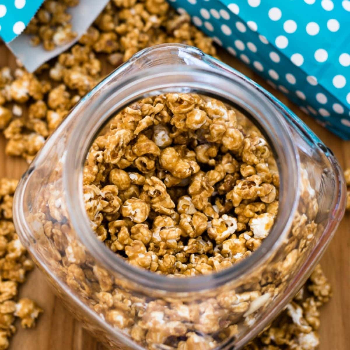 Overhead image of a glass candy jar filled with homemade caramel corn.