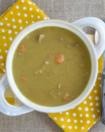 A white soup bowl with handles filled with Split Pea and Ham Soup.