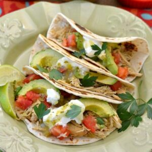 Three salsa Verde chicken tacos with toppings on a plate.